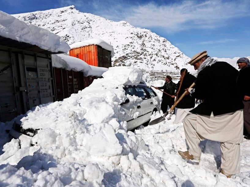 Homem afegão remove neve de cima de carro após avalanche em Panjshi, província do Afeganistão