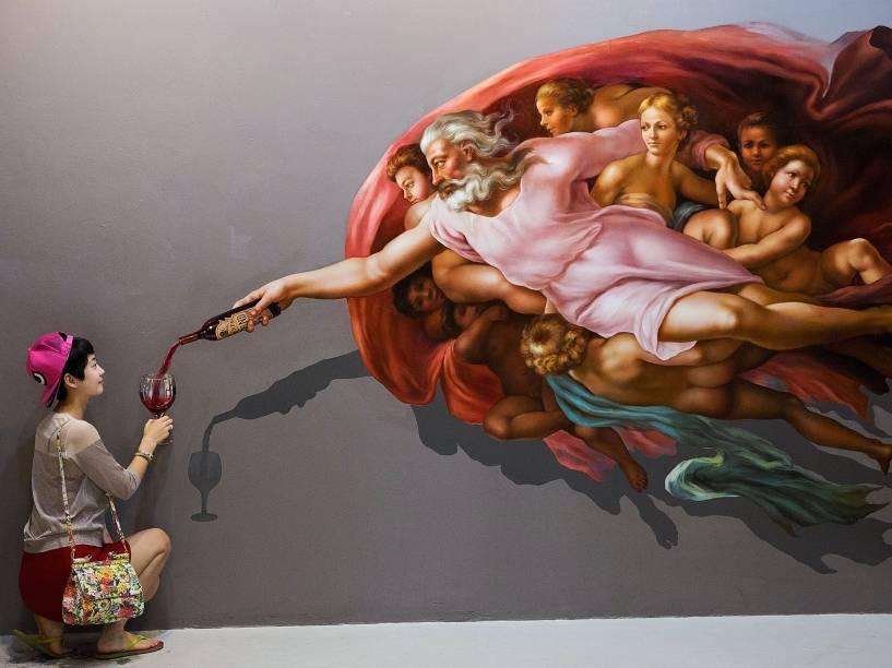 Turista chinesa se agaixa para posar para foto na exposição Art in Paradise no museu de arte ilusionária