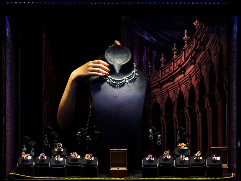 Mulher arruma jóias por detrás de vitrine para o envento International Jewellery Show, em Hong Kong