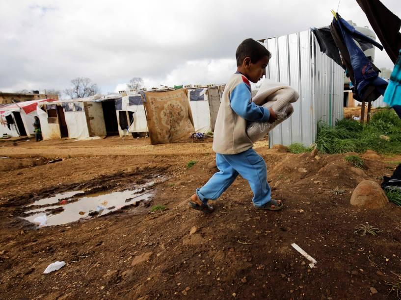 Garoto sírio carrega roupas que foram doadas por pela Inditex, empresa têxtil de grande porte espanhola, para o campo de refúgio na vila de al-Bireh, ao noroeste da cidade libanesa de Trípoli