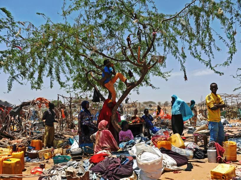 Somalis refugiados aguardam entre seus pertences espalhados após abrigo temporário ter sido destruído por soldados somalis, no campo Sarkusta, ao sudoeste de Mogadishu