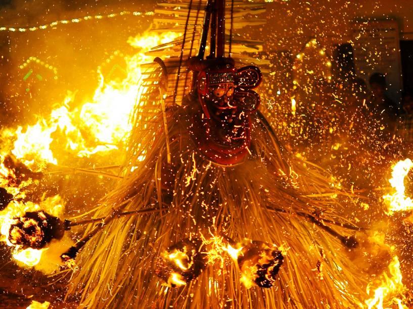 Artista vestido como o deus hindu Kandakarnan executa uma dança cerimonial com fogo durante ritual Theyyam na cidade de Somwarpet, no sul da Índia - 17/03/2015