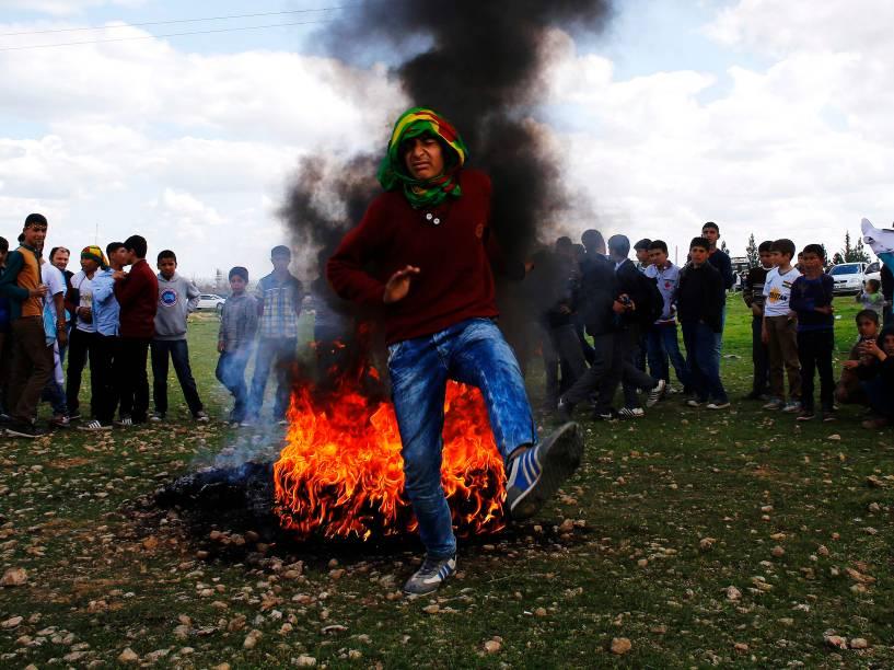 Jovem curdo salta sobre uma fogueira durante uma reunião celebrando Newroz, que marca a chegada da primavera e do novo ano, na cidade fronteiriça de Suruc na Turquia - 17/03/2015