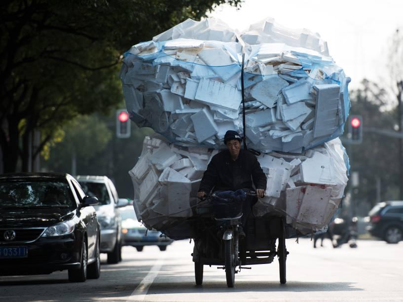 Homem anda sobre um triciclo carregado com inúmeras caixas de isopor em Xangai, na China - 17/03/2015
