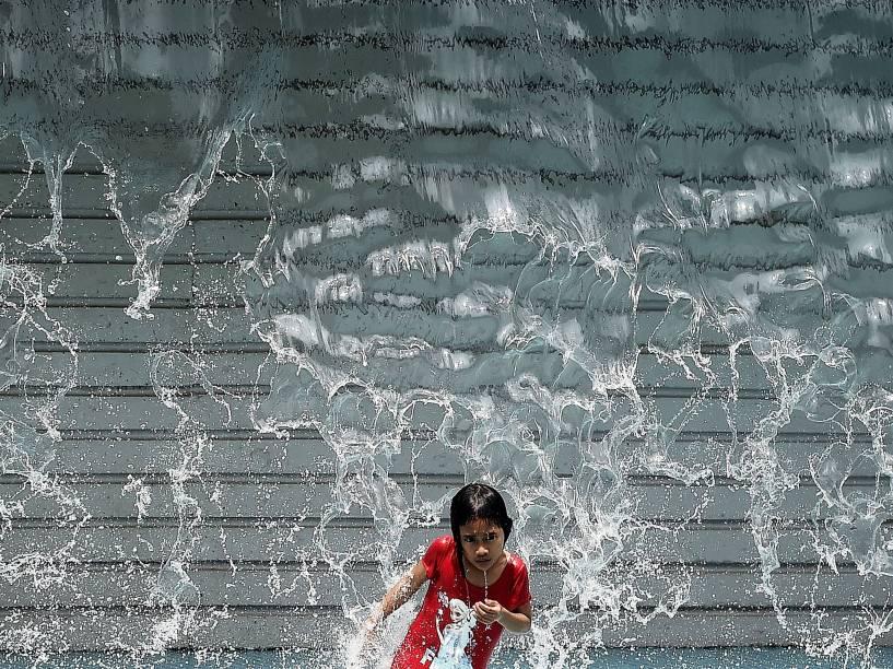 Menina se refresca em uma cachoeira artificial em Kuala Lumpur, na Malásia - 18/03/2015