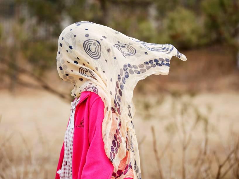 Mulher cobre rosto com um lenço para se proteger da poluição em um parque de Pequim, na China - 18/03/2015