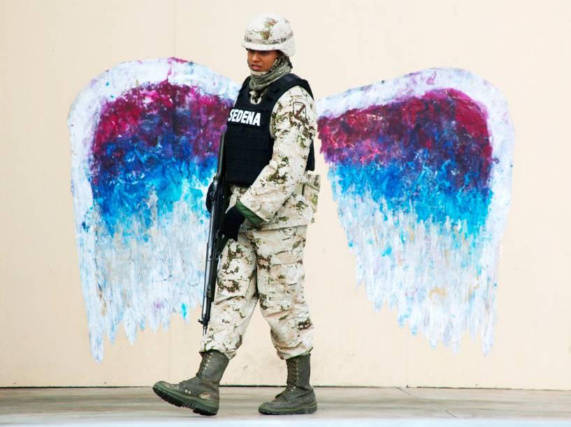 Soldado passa por um grafite de asas de anjo feito pelo artista Colette Miller, em Ciudad Juarez (México) - 19/03/2015