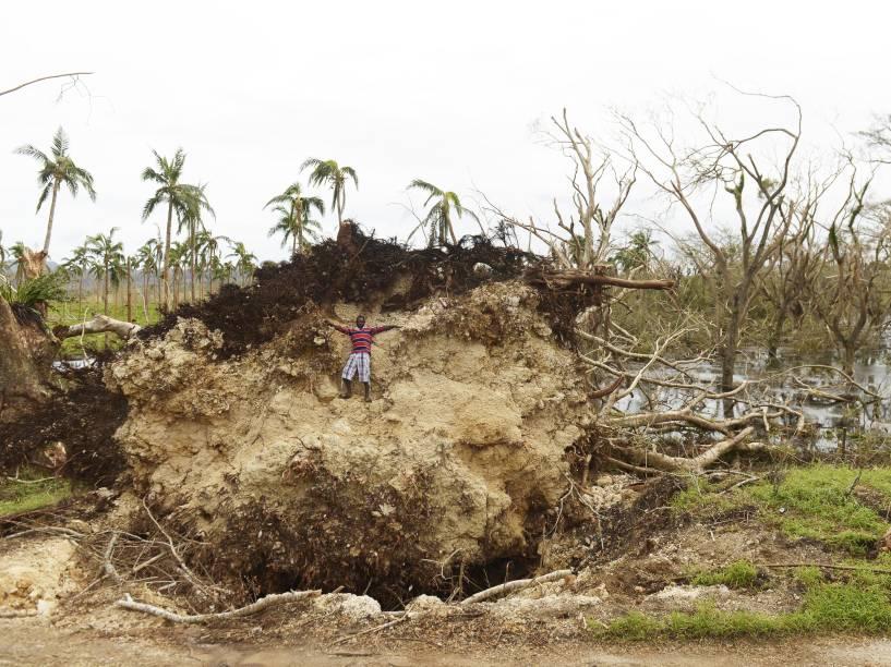Garoto sobe em bloco de terra que foi arrancado junto com as raízes de uma árvore pelos ventos do ciclone Pam, que passou por Port Vila, em Vanuatu (Pacífico do Sul) - 19/03/2015