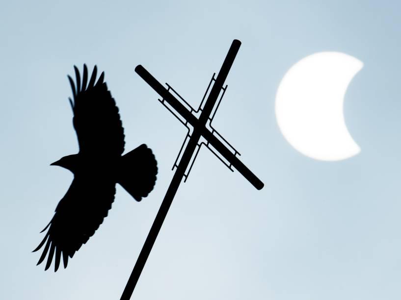 Pássaro voa próximo a crucifixo de uma igreja durante o eclipse solar, em Visselhoevede, noroeste da Alemanha - 20/03/2015