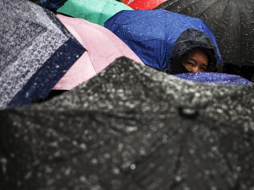 Homem olha para trás enquanto caminha em meio a pedestres com guarda-chuvas no início de uma nevasca na Times Square em Nova York - 20/03/2015