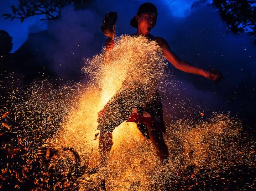 Homem chuta uma fogueira durante a celebração hindu do Mesabatan Api realizada anualmente um dia antes do Nyepi, Dia do Silêncio, que simboliza a purificação do universo e do corpo humano através do fogo, em Gianyar, Bali, na Indonésia - 20/03/2015
