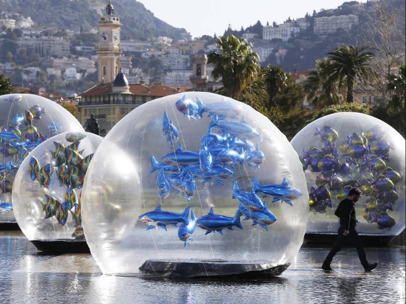 Homem caminhou ao lado de balões em forma de tubarão dentro de um globo de plástico em uma fonte de água em Nice, na França