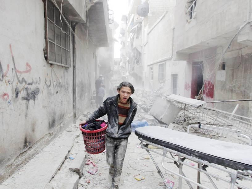 Garoto carregou seus pertences em local atingido por bomba jogada por forças leais ao presidente da Síria, Bashar al-Assad, na província de Aleppo