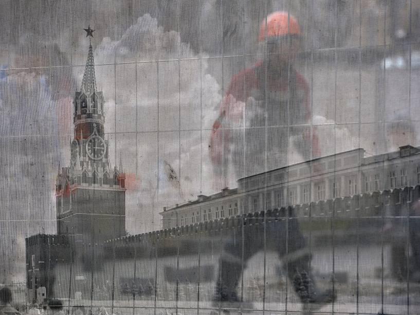 Trabalhador passa por trás de cerca transparente com imagem da Praça Vermelha, em uma construção em Moscou