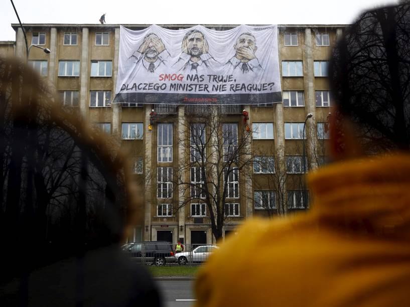"""Ativistas do Greenpeace são vistos colocando uma faixa no Ministério do Meio Ambiente com imagens do ministro, Maciej Grabowski. No cartaz está escrito: """"A poluição nos envenena, por que o ministro não faz nada?"""" - 08/04/2015"""