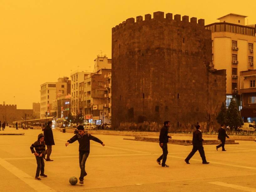 Meninos jogam futebol durante tempestade de poeira em Diyarbakir, na Turquia