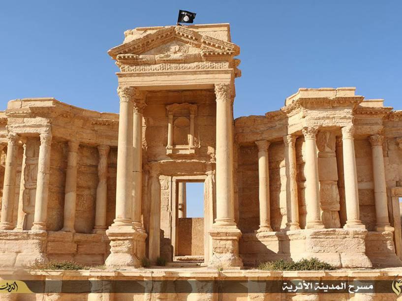 Imagem disponibilizada pelo veículo jihadista Welayat Homs, mostra uma bandeira do Estado Islâmico tremulando no alto do teatro romano da antiga cidade de Palmira, na Síria