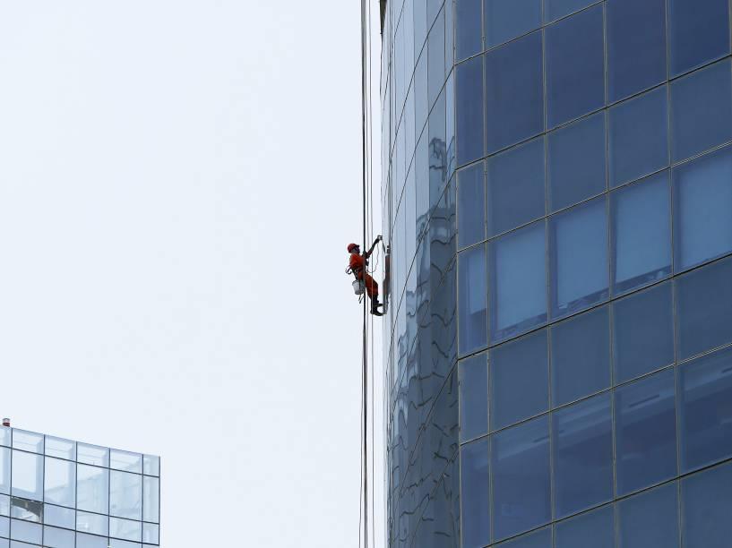Trabalhador limpa vidro de um edifício no centro de Gurgaon, na Índia - 29/05/2015