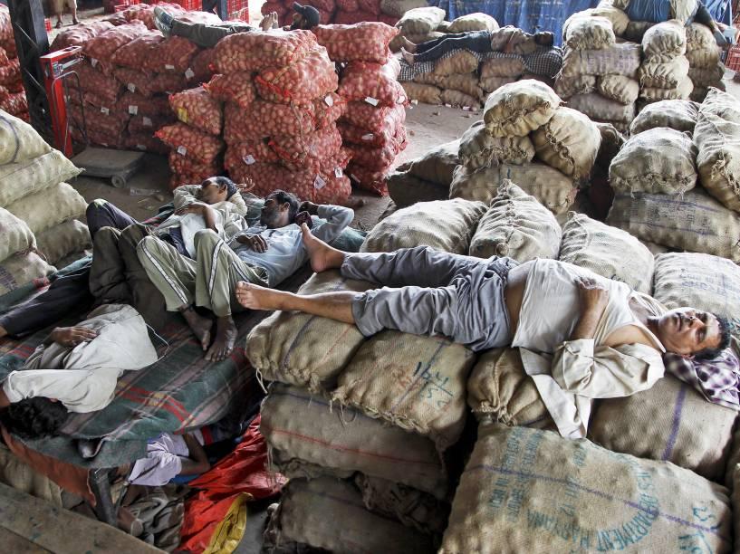 Vendedores tiram um cochilo sobre mercadorias em um mercado de Chandigarh, na Índia - 29/05/2015