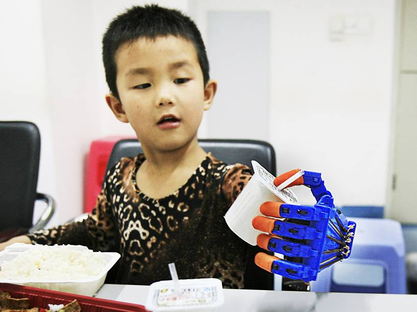 Xiaocheng, de 6 anos, pega uma caixa de iogurte com a mão protética feita por uma impressora 3D em um hospital de Wuhan, província de Hubei, China. O garoto teve a mão esquerda parcialmente amputada após sofrer um acidente de carro aos 4 anos - 29/05/2015