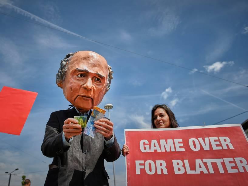 Manifestante vestindo uma máscara representando o presidente da FIFA, Joseph Blatter, segurando francos suíços durante protesto em frente ao Hallenstadium onde se realiza o congresso da entidade em Zurique, na Suíça - 29/05/2015