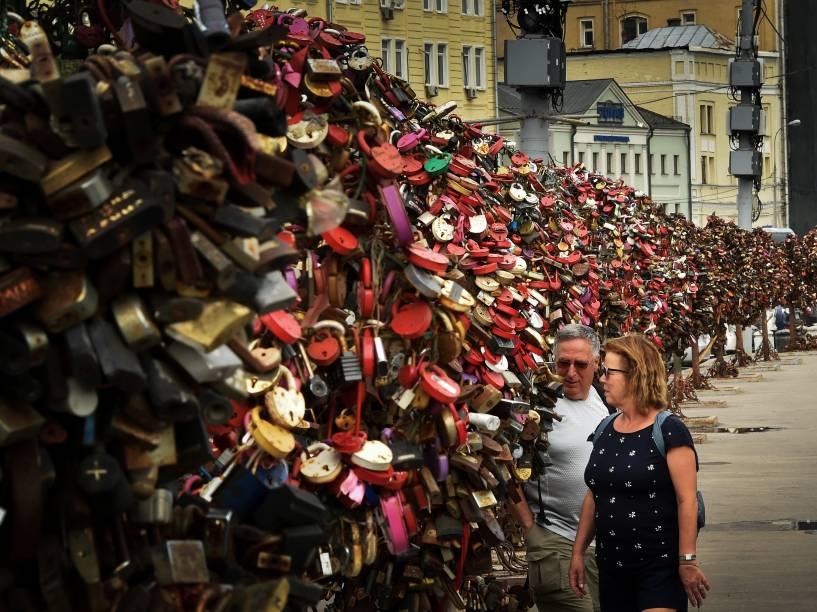 Casal caminha entre esculturas em forma de árvores repletas de cadeados no centro de Moscou, na Rússia - 29/05/2015