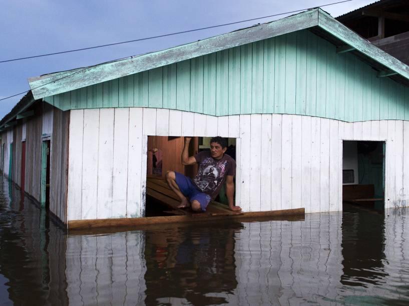 Homem se apoia sobre uma tábua em sua casa inundada pela cheia do Rio Solimões, um dos dois principais afluentes do rio Amazonas, em Anama, estado do Amazonas - 28/05/2015