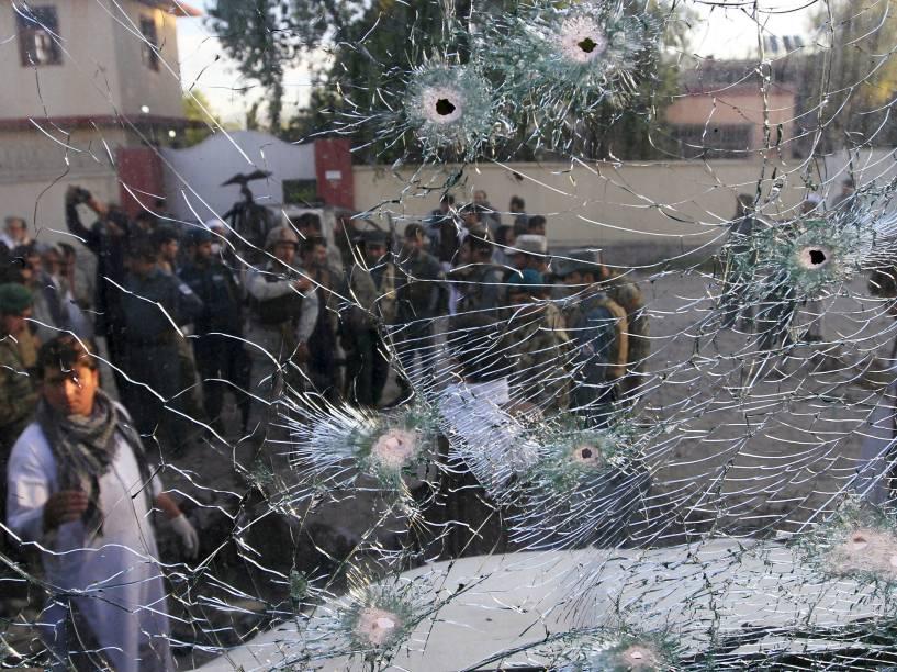Forças de segurança afegãs são vistas através da janela quebrada de um veículo, que foi danificado por um ataque suicída em um quartel de polícia em Jalalabad, Afeganistão - 01/06/2015