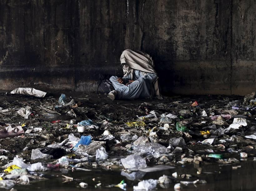 Usuário de drogas cobre a cabeça com um lenço debaixo de uma ponte habitada por viciados, em Cabul, Afeganistão - 01/06/2015