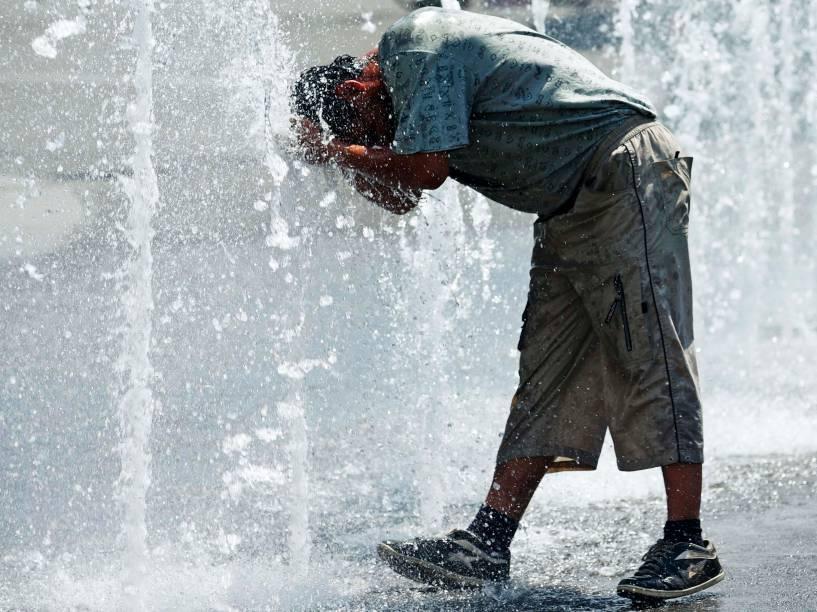 Homem se refresca em fontes de água em uma praça de Viena, Áustria - 08/06/2015