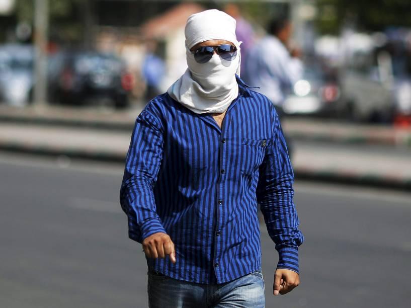 Homem caminha com o rosto coberto para se proteger do sol durante dia quente em Nova Déli. Segundo o departamento de meteorologia da Índia, a temperatura na cidade pode chegar aos 43 graus nos próximos dias - 08/06/2015