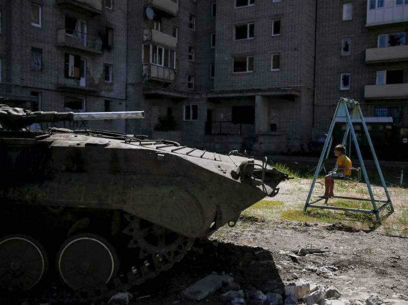 Menino senta-se em um balanço perto de seu prédio, danificado durante os combates entre o Exército ucraniano e separatistas pró-Rússia, na cidade Avdeyevka,  perto de Donetsk, leste da Ucrânia