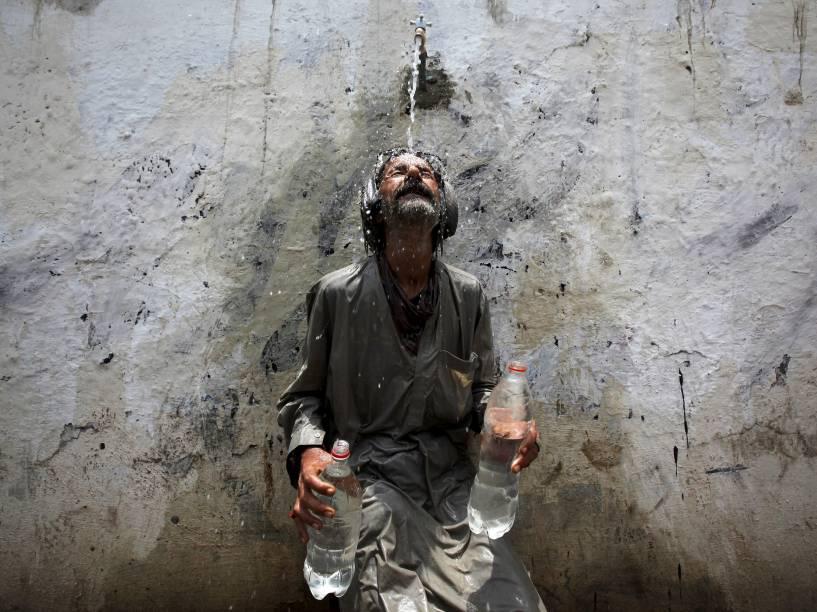 Homem se refresca em bica dágua em Karachi, no Paquistão. Onda de calor na cidade atinge os 45ºC - 23/06/2015