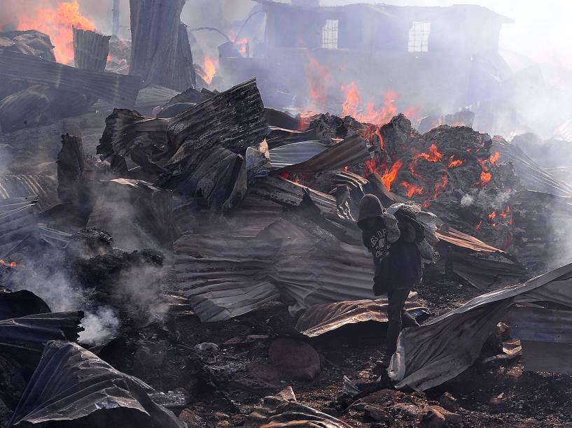 Garoto carregando metal para vender passa pelas chamas que queimam parte do mercado de Gikomba, maior mercado de roupas de segunda mão do leste da África, em Nairóbi - 23/06/2015