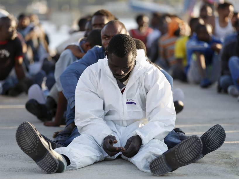 Imigrantes descansam após desembarcar em porto na região da Sicília, Itália. Barcos patrulhando o mediterrâneo encontraram mais de 2.700 imigrantes que navegavam em navios inseguros e sobrecarregados - 23/06/2015