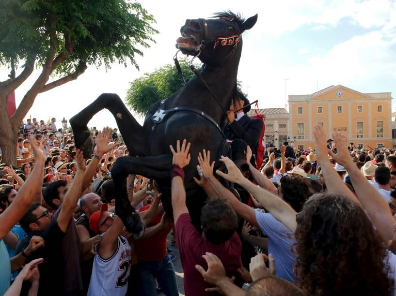 """Homem montado em cavalo é cercado por multidão durante a tradicional """"Fiesta of San Joan"""", em Ciutadella, Espanha - 23/06/2015"""