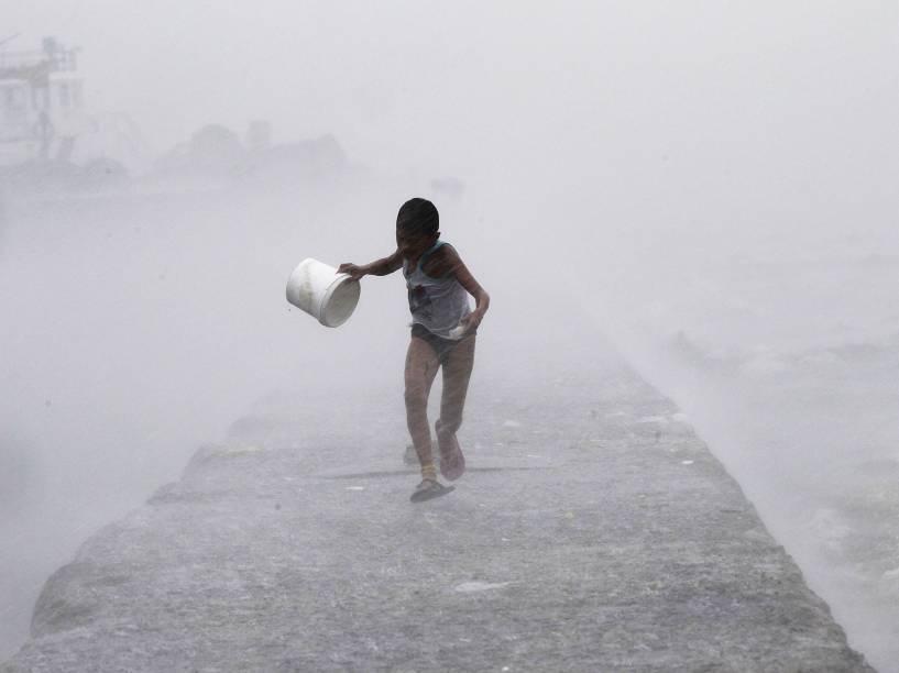 Durante forte chuva na baía de Manila, nas Filipinas, garoto correu enquanto era atingido por ondas trazidas pelo tufão Linfa, localmente conhecido como Egay