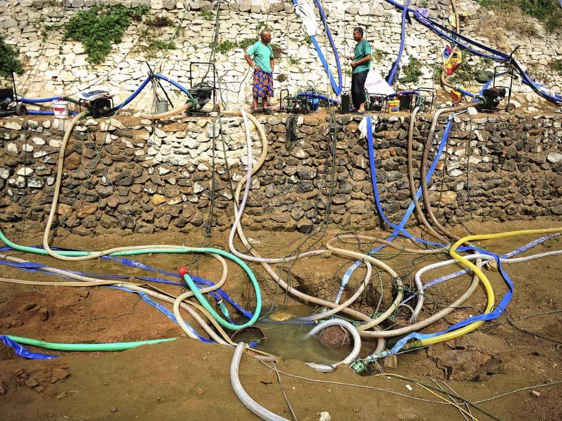 Moradores de Penglai, província de Shandong, na China, usam mangueiras para bombear água de buraco no meio de um poço quase seco. Segundo a mídia local, a região passa por forte seca devido à falta de chuvas desde a primavera - 08/07/2015