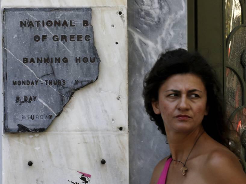 Mulher repousa ao lado de uma placa quebrada do Banco Nacional em Atenas, Grécia - 08/07/2015