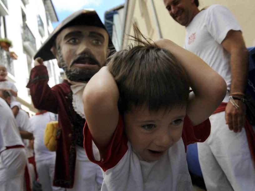 """Menino se protege de homem fantasiado durante a """"Parada dos gigantes e cabeçudos"""" no Festival de São Firmino, em Pamplona, Espanha - 08/07/2015"""