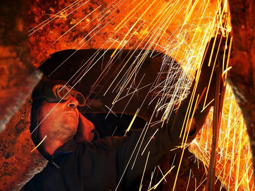 Homem trabalha no reparo do casco de um navio em um estaleiro na região portuária de Perama, em Pireu na Grécia. A região é uma das que mais sofrem com a crise econômica grega e apresenta altíssima taxa de desemprego - 08/07/2015