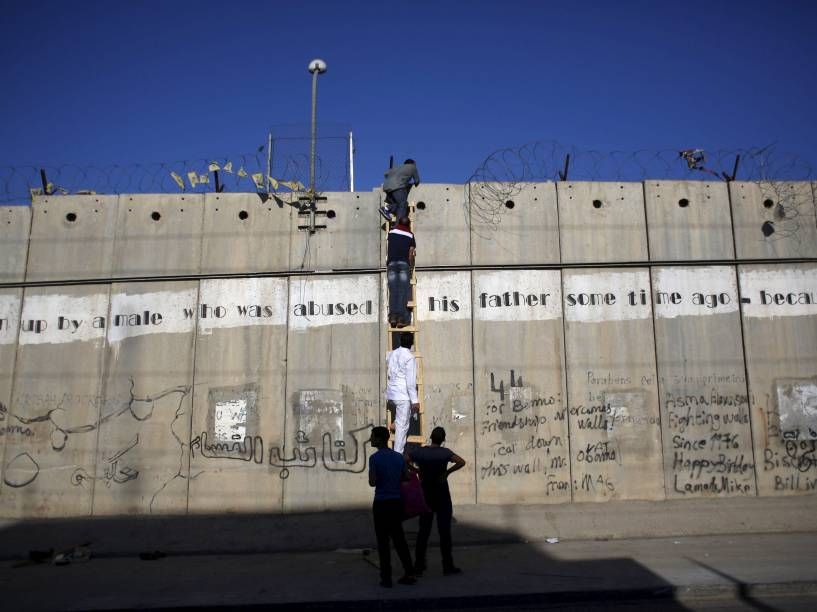 Palestinos impedidos de chegar a Jerusalém pelas forças de segurança israelenses usam uma escada para subir a controversa barreira feita por Israel, enquanto tentam participar da quarta reza de sexta-feira do Ramadan, na vila de Al-Ram - 10/07/2015