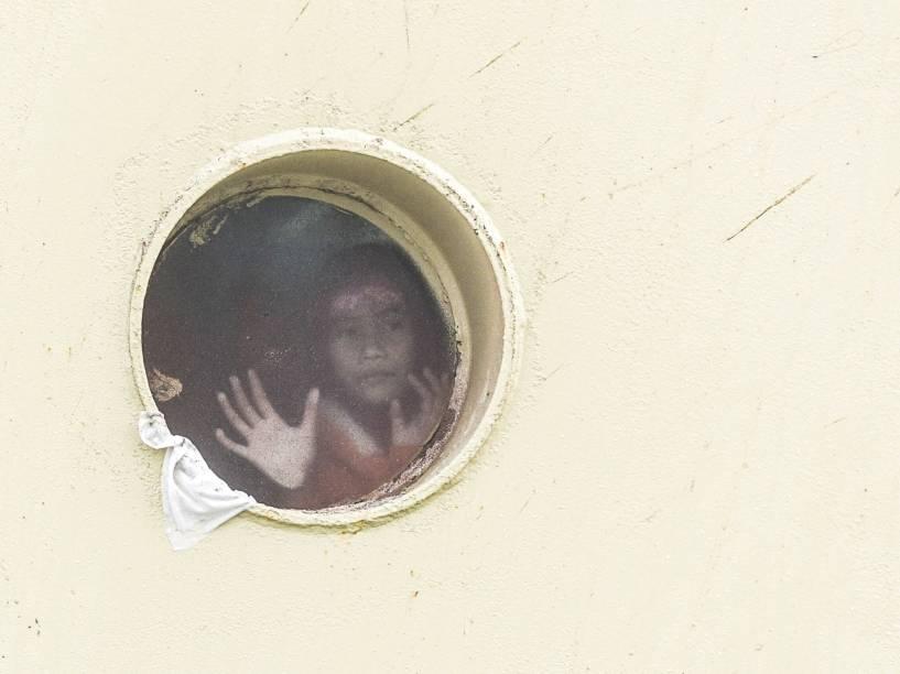 Garota olha pela janela de uma balsa antes de partir para Balikpapan, Indonésia. Milhões de muçulmanos indonésios pelo país partem das cidades principais de volta para suas casas para celebrar o fim do Ramadan com a família - 10/07/2015