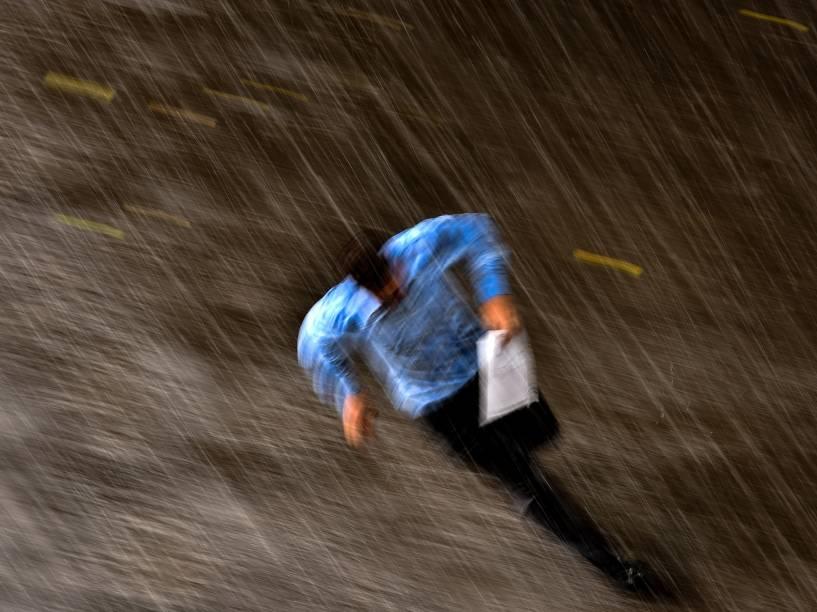 Homem corre debaixo da chuva pelas ruas do centro de Moscou, Rússia - 10/07/2015