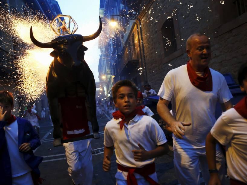 Homem carregando uma estrutura metálica em forma de um touro carregada com fogos de artifício, corre atrás dos foliões durante o festival de São Firmino, em Pamplona, norte da Espanha - 10/07/2015