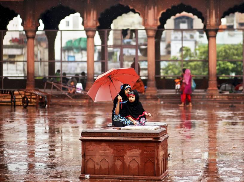 Meninas sentam-se sobre um móvel enquanto se protegem de forte chuva em Nova Délhi, na Índia - 10/07/2015