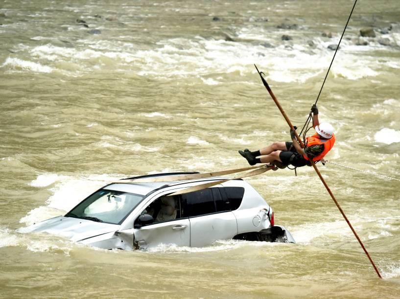 Membro de uma equipe de resgate tentou chegar até um carro ilhado no meio de um rio em Chongqing, na China. De acordo com a mídia local, mais de dez veículos caíram no rio após deslizamento devido à forte chuva na região
