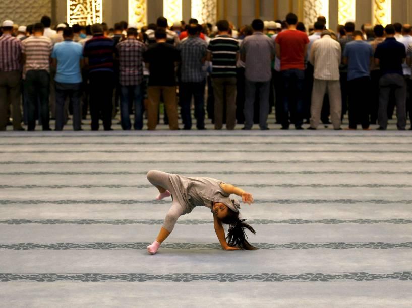 Menina foi fotografada brincando enquanto adultos faziam orações na mesquita de Ahmet Hamdi Akseki, em Ancara, capital da Turquia