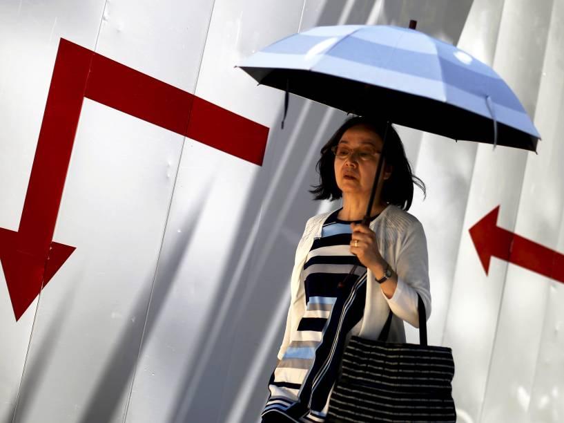 Japonesa foi fotografada caminhado com um guarda-chuva pelas ruas do distrito comercial de Tóquio, Japão