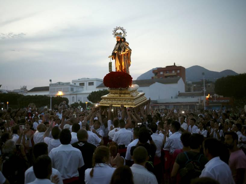 Homens em vestes tradicionais carregam a estátua de Nossa Senhora do Carmo, em processão que leva a estátua ao mar, em Málaga, Espanha - 16/07/2015